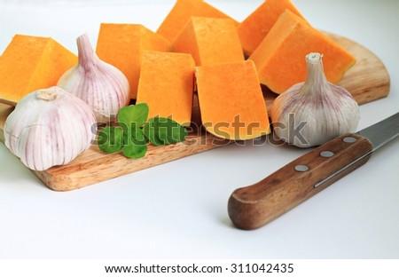 Fresh organic garden vegetables ingredients ripe pumpkin garlic bulbs basil aromatic herbs wooden kitchen utensils board knife preparing food light bright background  - stock photo