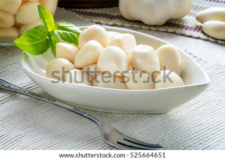 fresh organic garlic pickled, in a dish and a glass storage jar. whole and garlic cloves in the background . Blurred in parts for copy space