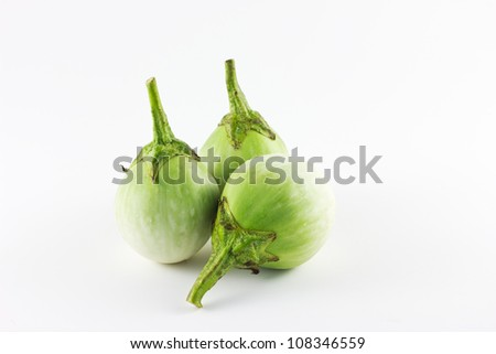 Fresh organic green eggplant with drops of water on white background
