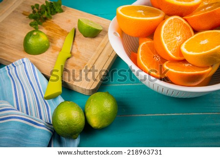 Fresh organic homemade orange and lemon juice preparation on rustic wooden kitchen table in vivid colour and blue background