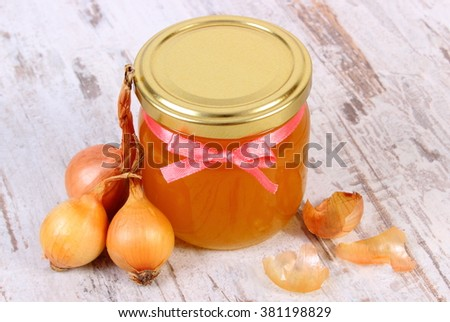 Fresh organic honey in glass jar and onions on old rustic wooden background, healthy nutrition, strengthening immunity and treatment of colds and flu - stock photo