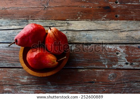 Fresh organic juicy pears in bowl on rustic wood. Pear autumn harvest. Fruit background. Top view. - stock photo
