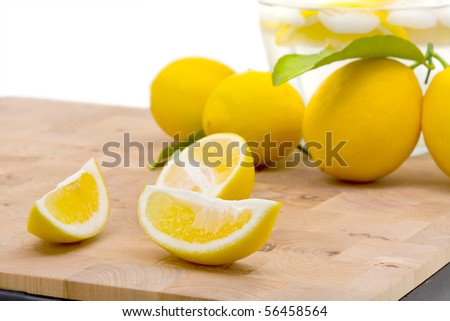 Fresh organic lemons with leaf over white background - stock photo