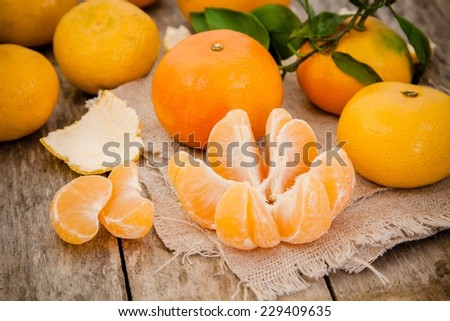fresh organic mandarins and peeled slices on a rustic wooden background - stock photo
