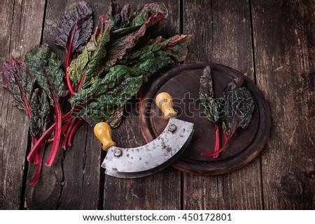 Fresh organic Mangold over a rustic wooden board with mezzaluna - stock photo