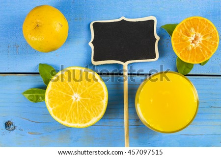 Fresh organic orange and juice on rustic wooden kitchen table in vivid color and blue background - stock photo