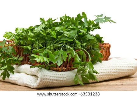Fresh organic parsley in basket on wooden table