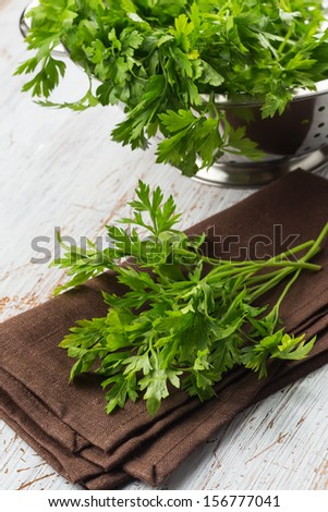 Fresh organic parsley in bowl on white wooden background. Selective focus.