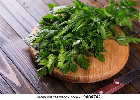 Fresh organic parsley on cutting board on wooden background. Selective focus, horizontal.
