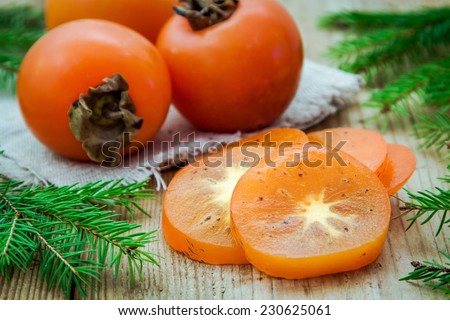Fresh organic persimmon with slices on wooden background with pine tree - stock photo