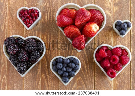 Fresh organic pomegranate seeds, blackberries, raspberries, blueberries and strawberries arranged in heart shapes on wooden table - stock photo