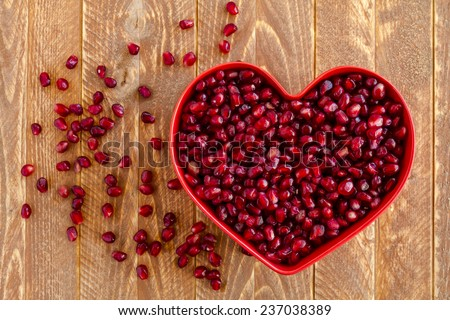 Fresh organic pomegranate seeds in red heart shaped bowl sitting on wooden table - stock photo