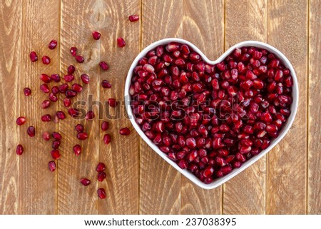 Fresh organic pomegranate seeds in white heart shaped bowl sitting on wooden table - stock photo
