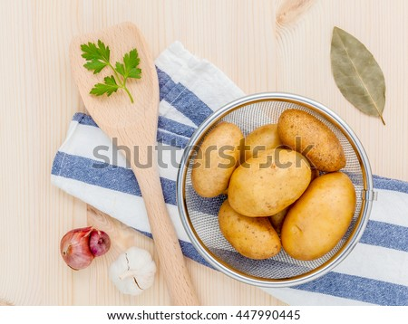 Fresh organic potatoes in basket with herbs garlic,shallot ,parsley and bay leaves on rustic wooden table. Preparation for cooking.