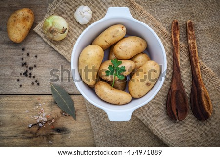 Fresh organic potatoes in white ceramic bowl with ingredients and herbs  , parsley, garlic, bay leaves, pepper, onion and himalayan pink salt on hemp sake and rustic wooden table .  - stock photo
