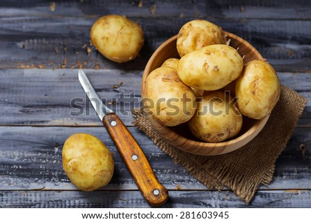 Fresh organic potatoes in wooden table. Selective focus - stock photo