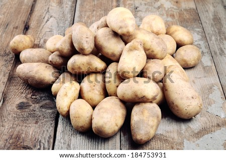 Fresh organic potatoes on a wooden table. - stock photo