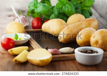 Fresh organic potatoes with herbs on a wooden background, selective focus, rustic style - stock photo