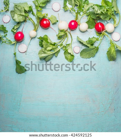 Fresh organic radishes from garden on blue wooden background, top view, border - stock photo