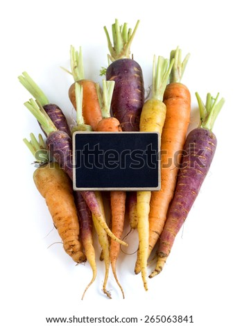 Fresh organic rainbow carrots with small chalkboard isolated on white - stock photo