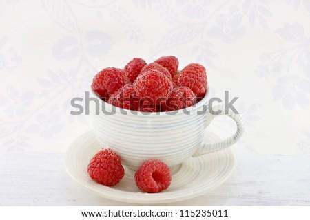 Fresh organic raspberries in a coffee cup. - stock photo