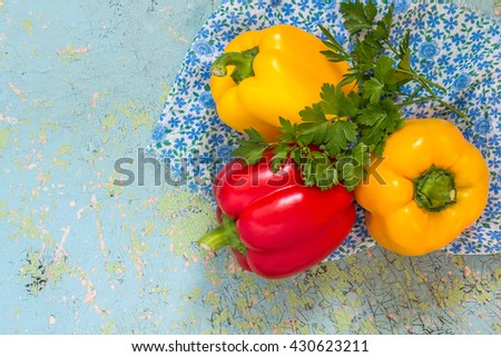 Fresh organic red and yellow bell peppers and parsley on old blue table - stock photo