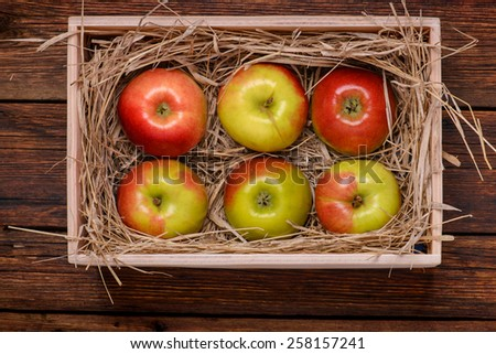 Fresh organic red apples in box on wooden table close-up - stock photo