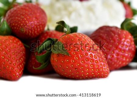 Fresh organic red strawberries with whipped cream select focus at strawberries
