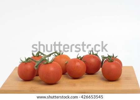 Fresh organic red tomatoes on brown wooden platform isolated on white background.