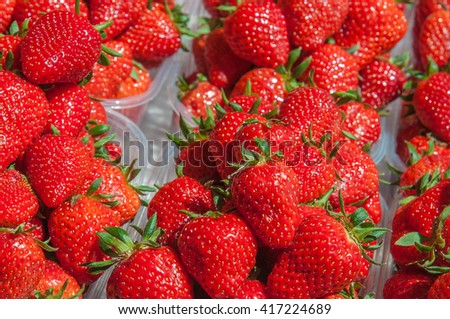 Fresh organic ripe fresh juicy strawberries in plastic boxes background closeup