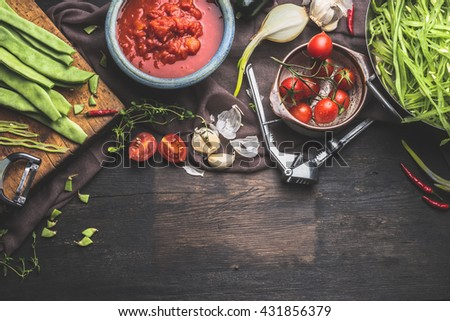 Fresh organic seasonal vegetables on dark rustic wooden background. Tomatoes ,  Green french beans and cooking ingredients for tasty vegetables dish. Vegan and healthy food concept - stock photo