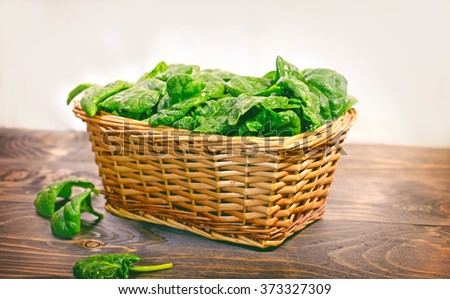 Fresh organic spinach in wicker basket - stock photo