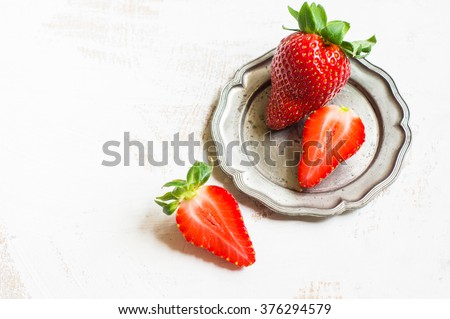 Fresh organic strawberries in vintage plate on  rustic background