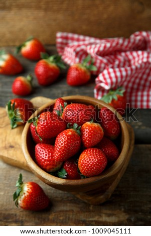 Fresh organic strawberry in rustic wooden bowl