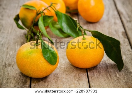 fresh organic tangerines with leaves on a rustic wooden background - stock photo
