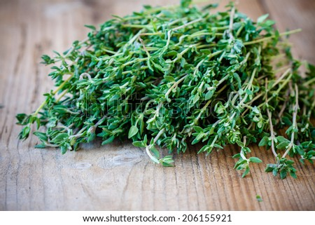 fresh organic thyme on a wooden background - stock photo