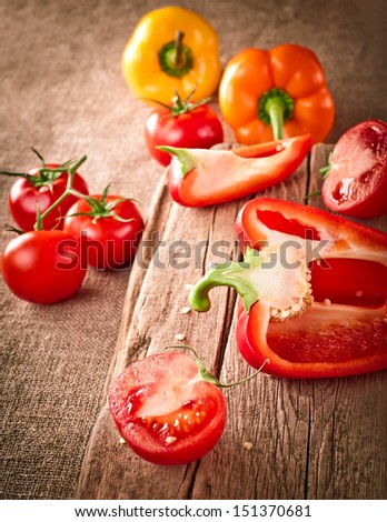 Fresh organic tomatoes and paprika, at wooden cutting board on canvas tablecloth. Image in vintage style - stock photo