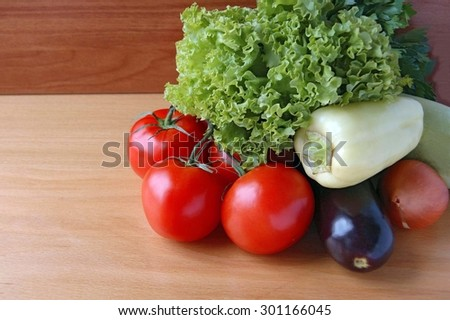 Fresh organic  tomatoes, eggplant. pepper, salad lettuce on a wooden table top - stock photo