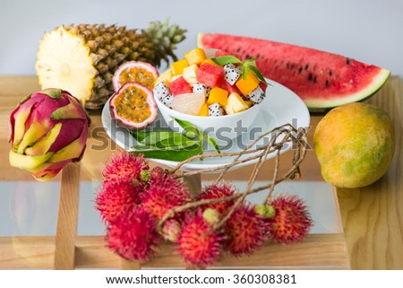 Fresh organic tropical fruits on the table and bowl of salad - stock photo