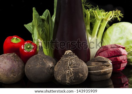Fresh organic vegetable still life. Black radish, purple eggplant, capsicum, fennel, cabbage and chinese cabbage isolated on black background. Colorful vegetarian and vegan healthy eating variation. - stock photo