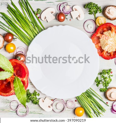 Fresh organic vegetables and seasoning ingredients for tasty vegetarian cooking around blank white plate , top view. Healthy or diet food concept. - stock photo