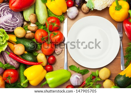 Fresh Organic Vegetables Around White Plate with Knife and Fork / copy space for text - stock photo