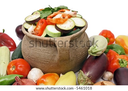 Fresh organic vegetables in a clay pot - stock photo