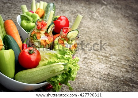 Fresh organic vegetables in jar and in bowl - stock photo