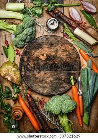 Fresh organic vegetables ingredients for soup or broth around round rustic blank cutting board, top view. Healthy food or vegetarian cooking concept. - stock photo
