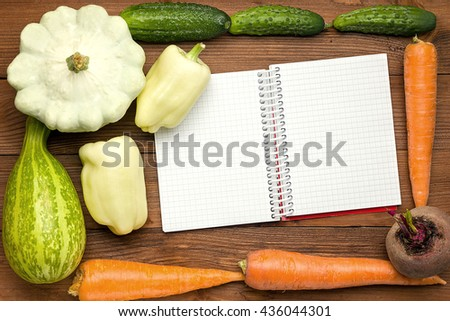 Fresh Organic Vegetables on a Wooden Background and Paper for Notes. Open Notebook and Fresh Vegetables Background. Diet. Health food. Space For Your Text. - stock photo