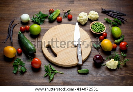 Fresh Organic Vegetables on awooden table with cutting board and Knife - stock photo