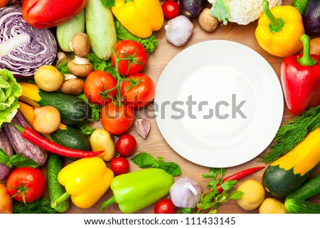 Fresh Organic Vegetables on wooden Table Around White Plate / with copy space for your text - stock photo