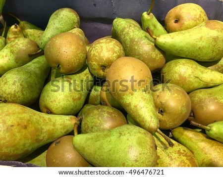 Fresh organic yellow pear stand out among many large background pears in the market. Fruit of yellow pear. Close-up pears texture.