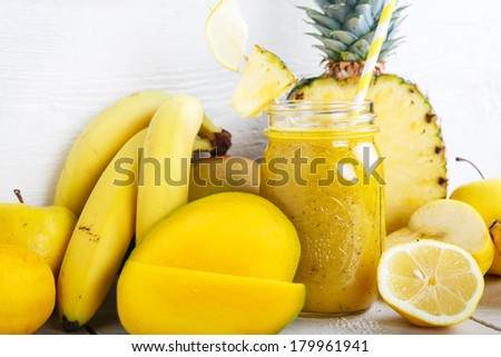 Fresh organic yellow smoothie with banana, apple, mango, pear, pineapple and lemon as healthy drink - stock photo